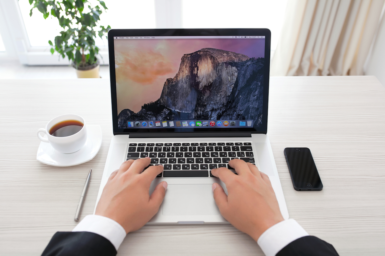 Businessman Sitting At The Macbook Pro Retina With Osx Yosemite On The Screen In The Office
