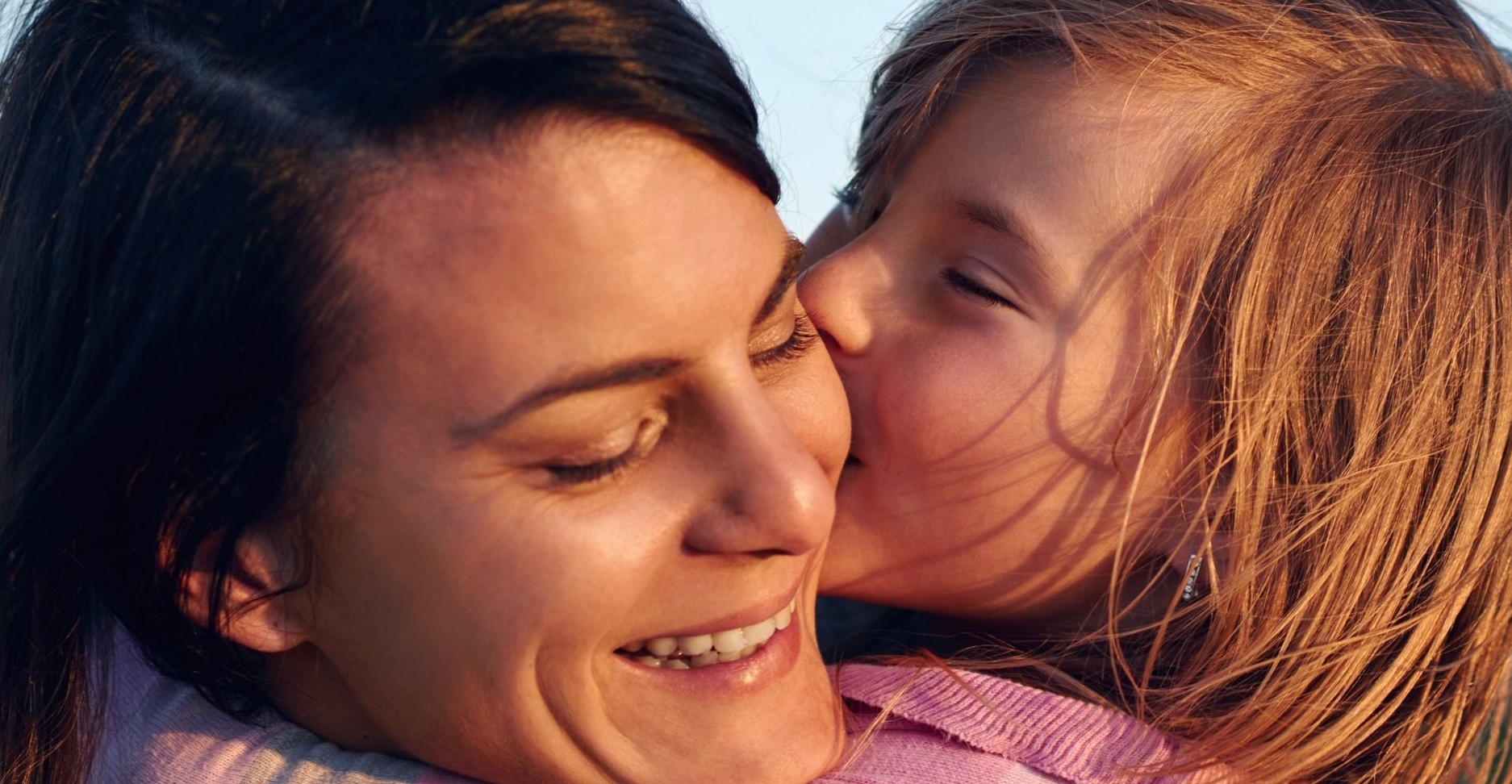 Daughter kissing mum on the cheek outside