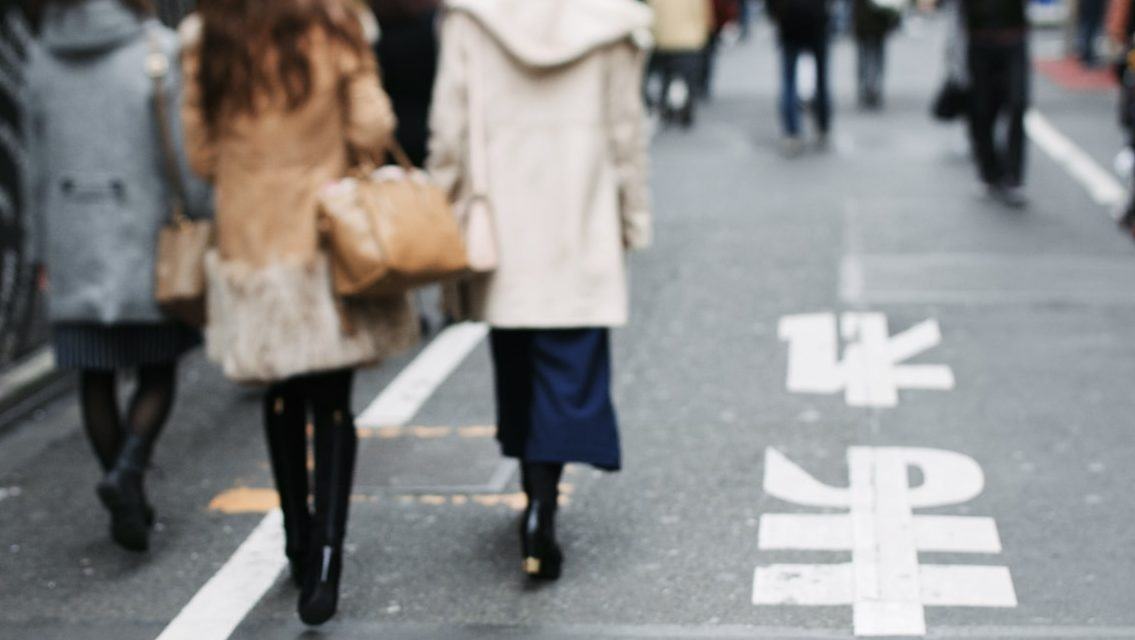3 females out of focus walking on footpath in the city among other pedestrians