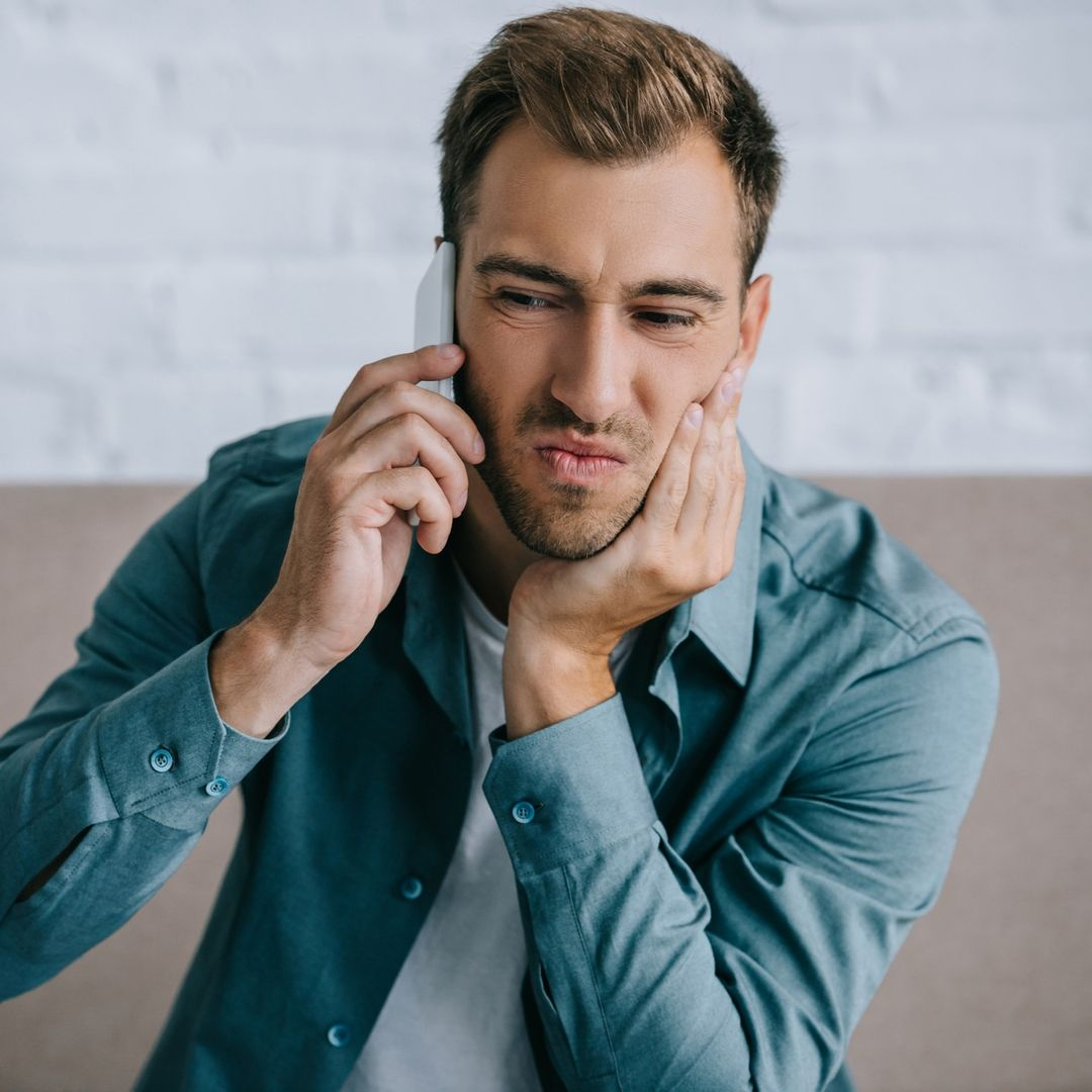 Young male on phone clutching jaw with a scrunched facial expression representing pain.