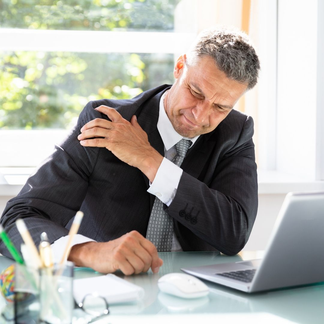 Middle aged male office worker clutching shoulder in pain, while sitting at desk