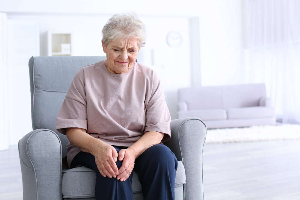 Elderly woman suffering from pain in knee at home